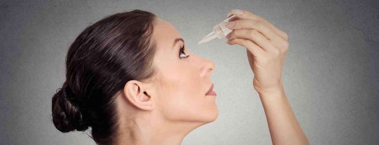 Alergiczne zapalenie spojówek - kobieta używająca kropli do oczu.